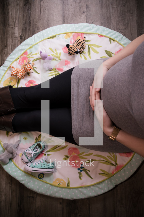 pregnant mother sitting on a nursery room rug