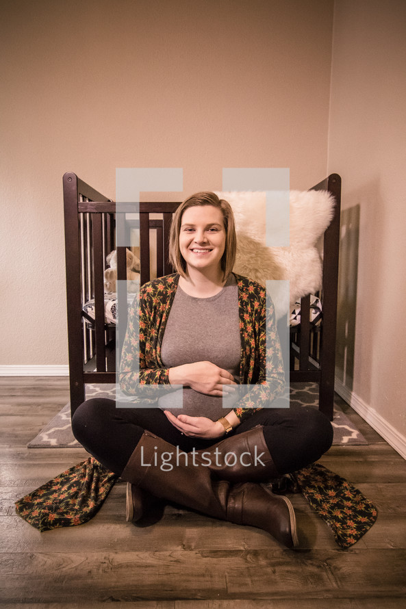 pregnant woman sitting on the floor of a nursery holding her belly