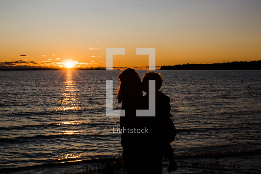 silhouette of mother and son at sunset