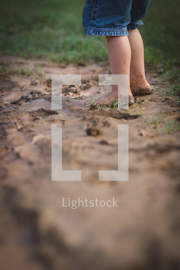 child's bare feet in mud