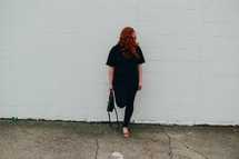 redhead woman standing in front of a white wall