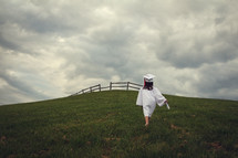 girl walking up a hill carrying a diploma