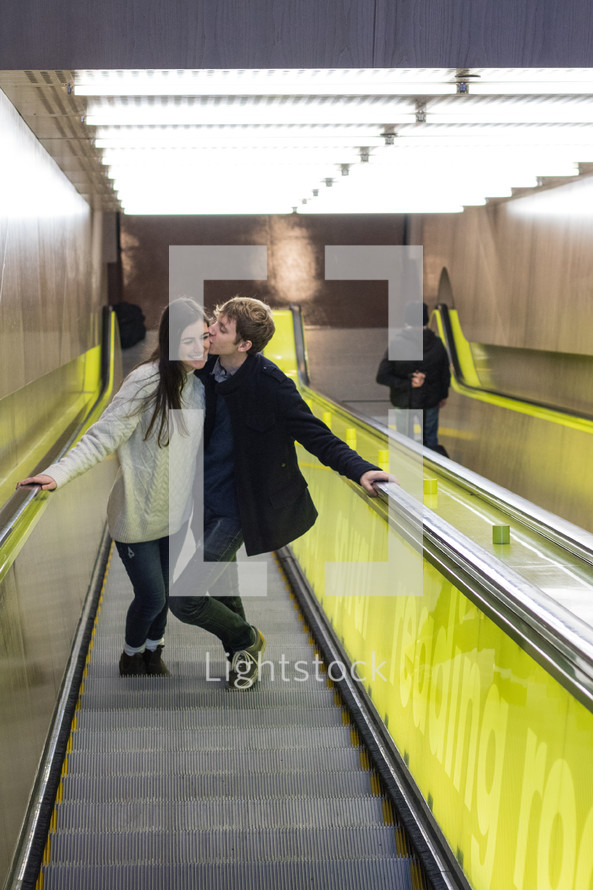 kissing couple on an escalator