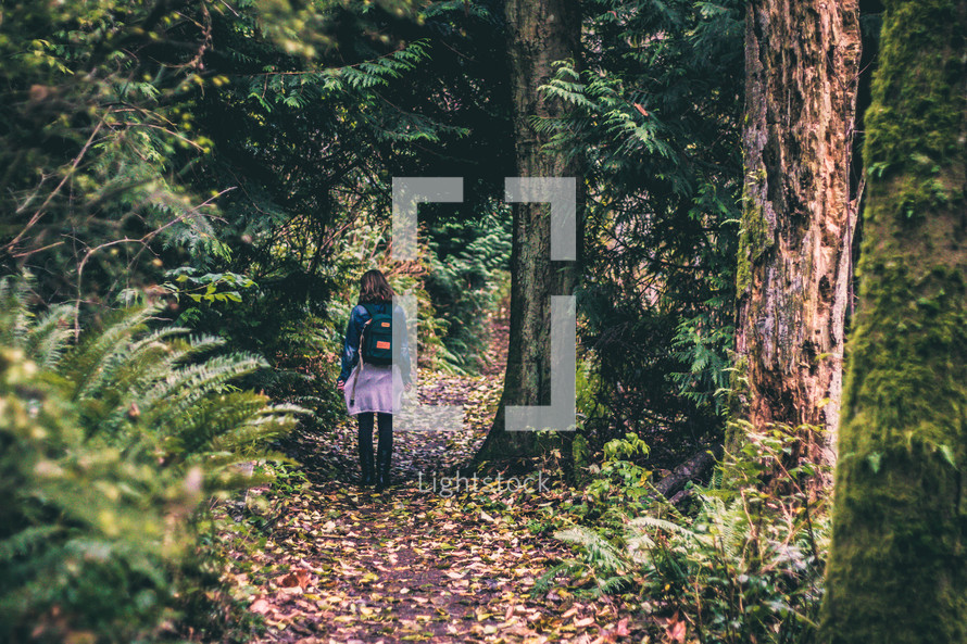 girl with a backpack walking into the woods