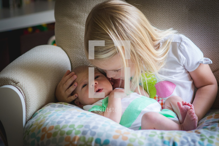 a sister kissing her baby brother