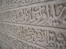 Words carved in a stone wall in Jordan