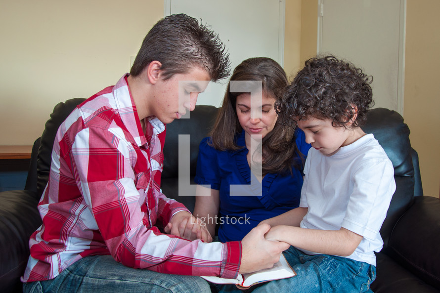 Mother praying with sons over the Bible at home.