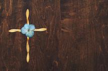 cross of flower petals on wood