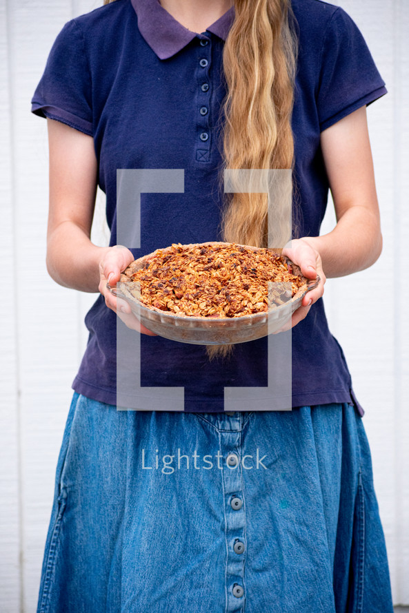 girl holding a casserole dish