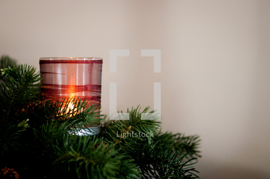 A Christmas centerpiece and candle.