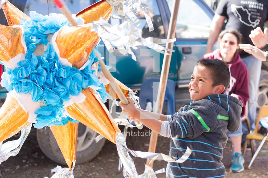 A boy hitting a star shaped piñata.