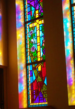 Morning sunlight and sun rays pour through a beautiful and colorful stained glass window showing a light prism of colors through a large stained glass window of the cross in the morning sunlit church service.