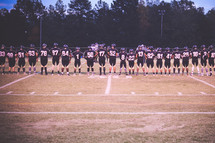 football team praying on the sidelines