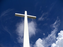 A white cross towers over the earth, sky and clouds reaching out to Heaven against a blue sky on a bright sunny day giving hope to all who see it that there is a God who came down from Heaven to be with us and take our place on this very cross for our sins that we might be saved and spend eternity in Heaven with Jesus.