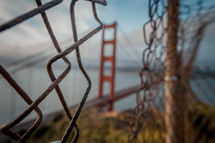 Focus on a hole in a fence in front of Golden Gate Bridge
