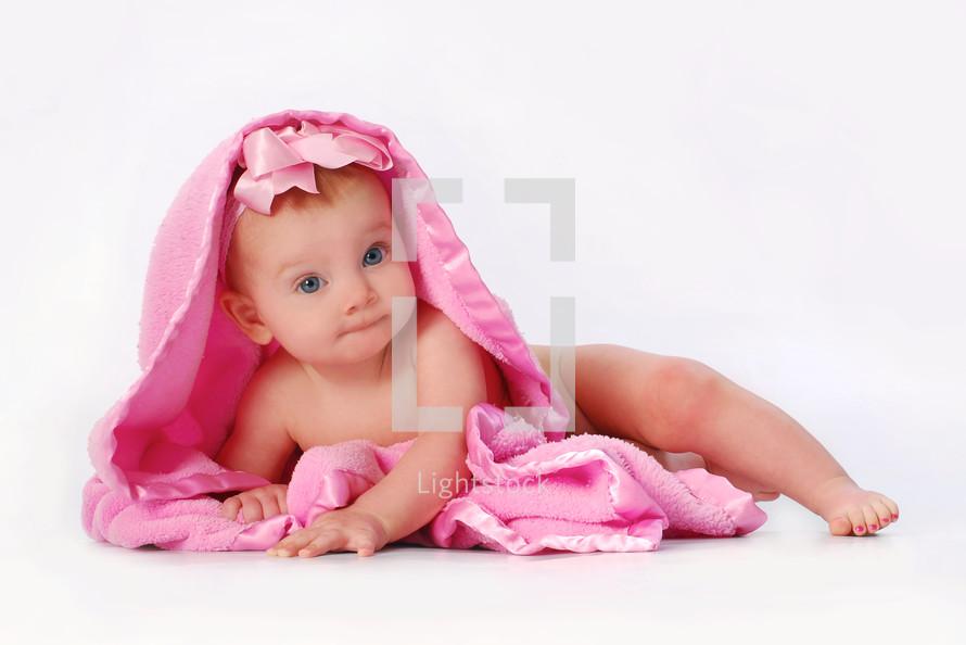 infant girl under a pink blanket