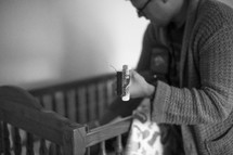 a father playing a guitar to a baby in a crib