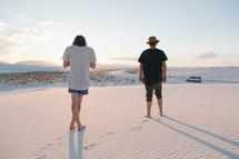 men standing barefoot on sand dunes