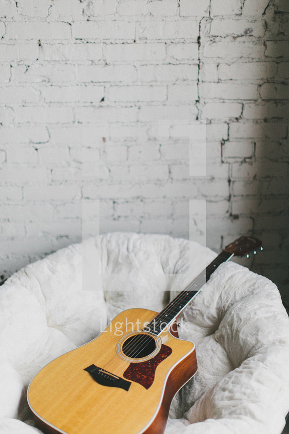 guitar resting in a bucket chair
