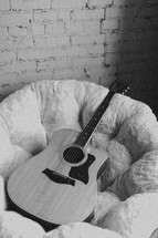 acoustic guitar resting in a bucket chair