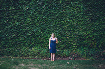 A woman standing in front of an ivy covered wall.