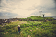 woman walking up to a lighthouse