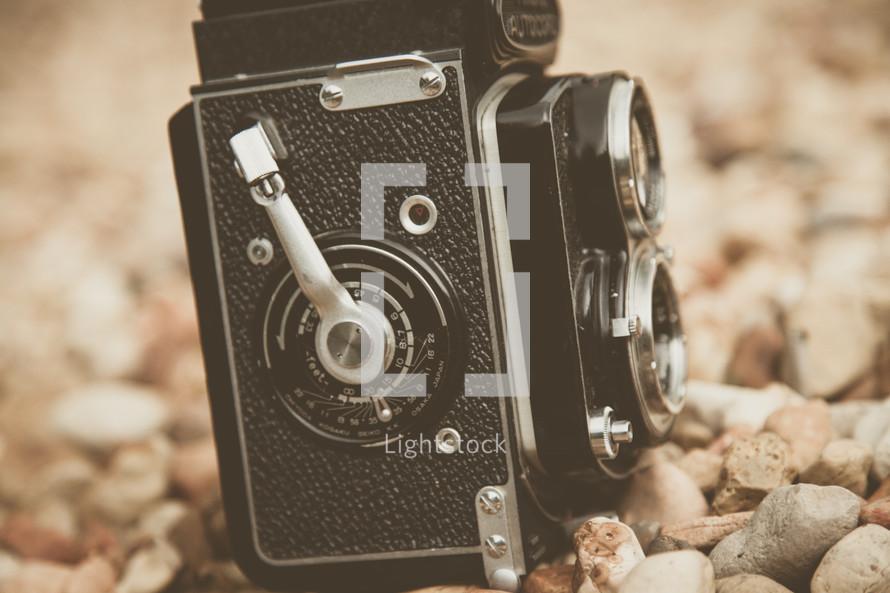 a vintage camera in rocks