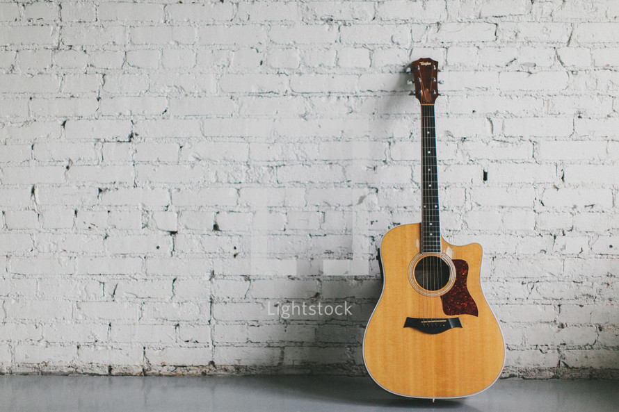 guitar resting against a brick wall painted white