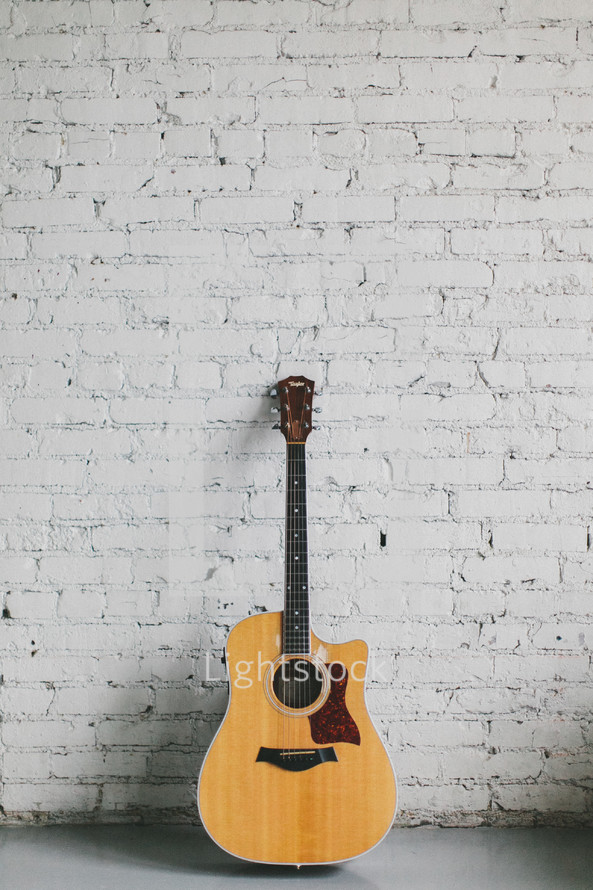 acoustic guitar resting against a brick wall painted white