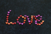 The word LOVE written with many little colorful clay hearts on black background.