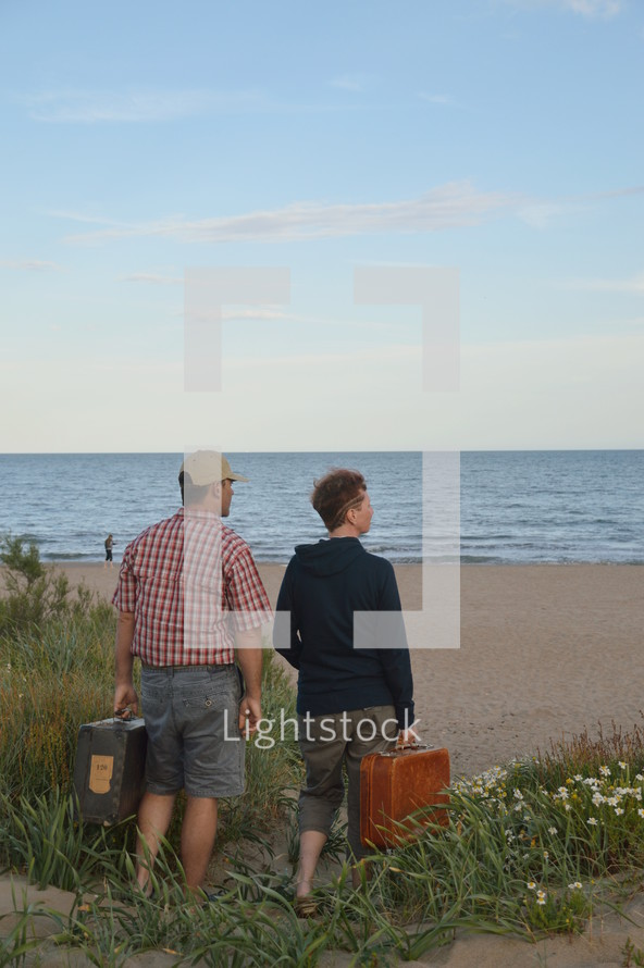 a couple with suitcases looking out at a beach