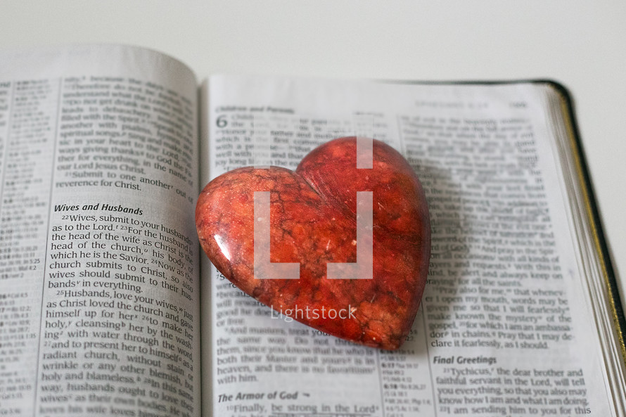 red heart shaped stone on the pages of a Bible