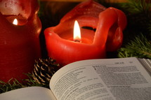 bible open to Luke 2: The Birth of Jesus with burning candles in advent. 