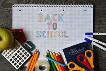 """Colorful school supplies on a notebook which reads, """"Back to School."""" school, supplies, paper, college block, blank, notebook, exercise book, checkered, squared, plaid, apple, bible, new testament, sharpener, pencil, pencil  sharpener, lead pencil, pencils, colored pencil, crayon, scissors, shear, clippers, shears, color, kids, back, back to school, colorful, children, little, happy, cheerful, learn, learning, teach, teaching, teacher, jolly, bright, joy, young, infant, youngster, youngsters, infants, offspring, yellow, orange, red, blue, green, black, write, writing, read, reading, kid, multicolored, fun, educate, education, parent, parents, childhood, pupil, pupils, first-grader, first-former, schoolchild, child, student, schoolkid, school kid, school child, schoolday, school day, first, first day in school, enrollment, enrolment, begin, beginning, term, start, starting, scholar, schoolboy, schoolboys, disciple, disciples, attend, attending, attendance, multicolored, pen, homework, childlike, naive, table, wood, wooden, folder, loose-leaf binder, ink eradicator, ink eraser, sticky tape, letters, letter, word, words, written"""