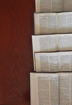 Bibles in different languages lying open on a table.