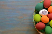 He is Risen scripture in brightly colored Easter Eggs in a basket on cyan wood background