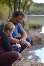 father and son together on a lake shore