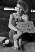 a homeless woman holding a sign - no money no job no hope