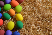 Colorful Easter eggs on a bed of straw.