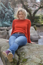young pretty blond woman with orange pullover sitting outdoors in a park on a mossy rock smiling