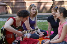friends sitting on a blanket in the grass singing songs of praise