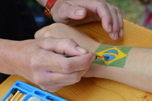 woman painting a brazilian flag on someones arm.