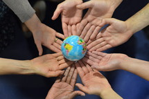 international group holding a globe together. \