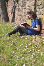 Woman reading the bible while sitting in a meadow next to a stone wall.
