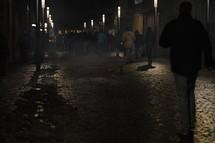People walking on an illuminated city street by night between snow slush and trash.