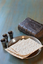 The Lord's Supper with bread, wine and an ancient bible.