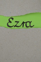 torn open kraft paper over green paper with the name of the book Ezra