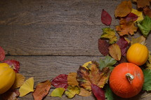 colorful autumn leaves and pumpkins on old wooden floorboards