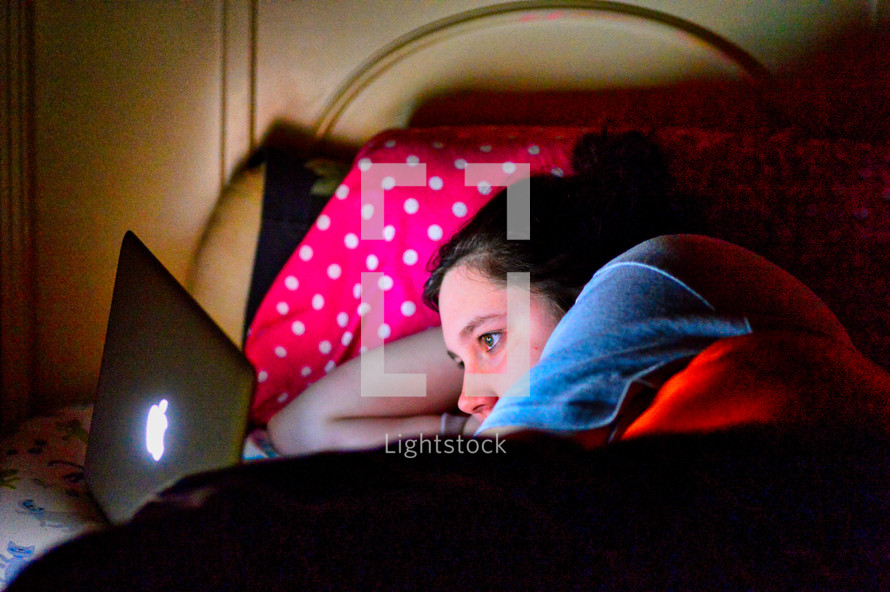 teen girl looking at a computer screen laying in bed