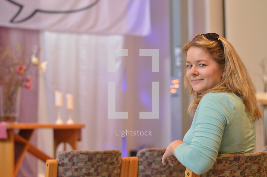 a young blond woman sitting at a chair in a modern church before the service starts turning around and looking back over her shoulder. - useful for church reopening: welcome back to church